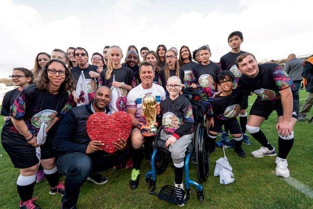 Les enfants de l'association avec la Coupe du monde ramenée par Deschamps